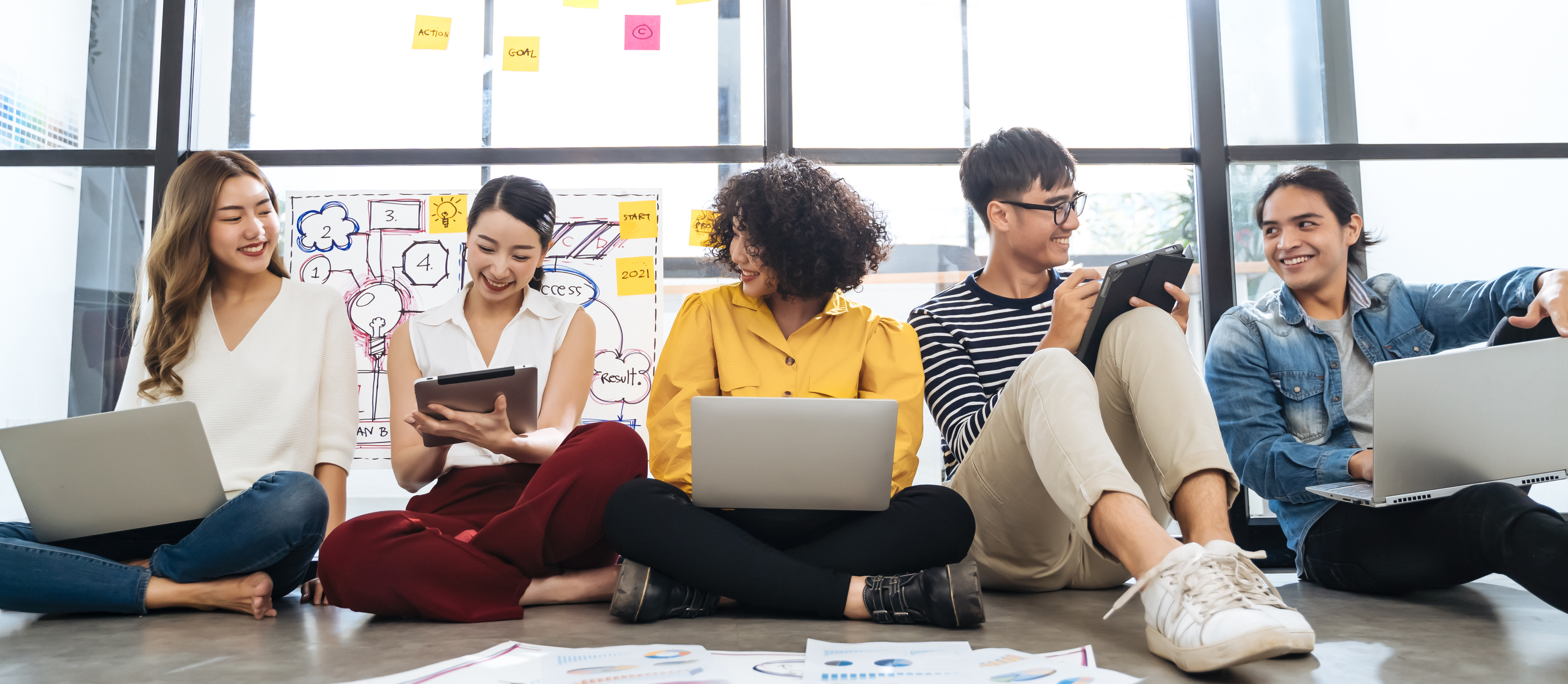 Group of young happy Asian creative business people or hipster student using electronic devices tablet and laptop connection together in modern office. Creative lifestyle young people concept