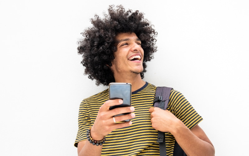 happy young guy with bag and cellphone smiling on isolated white background
