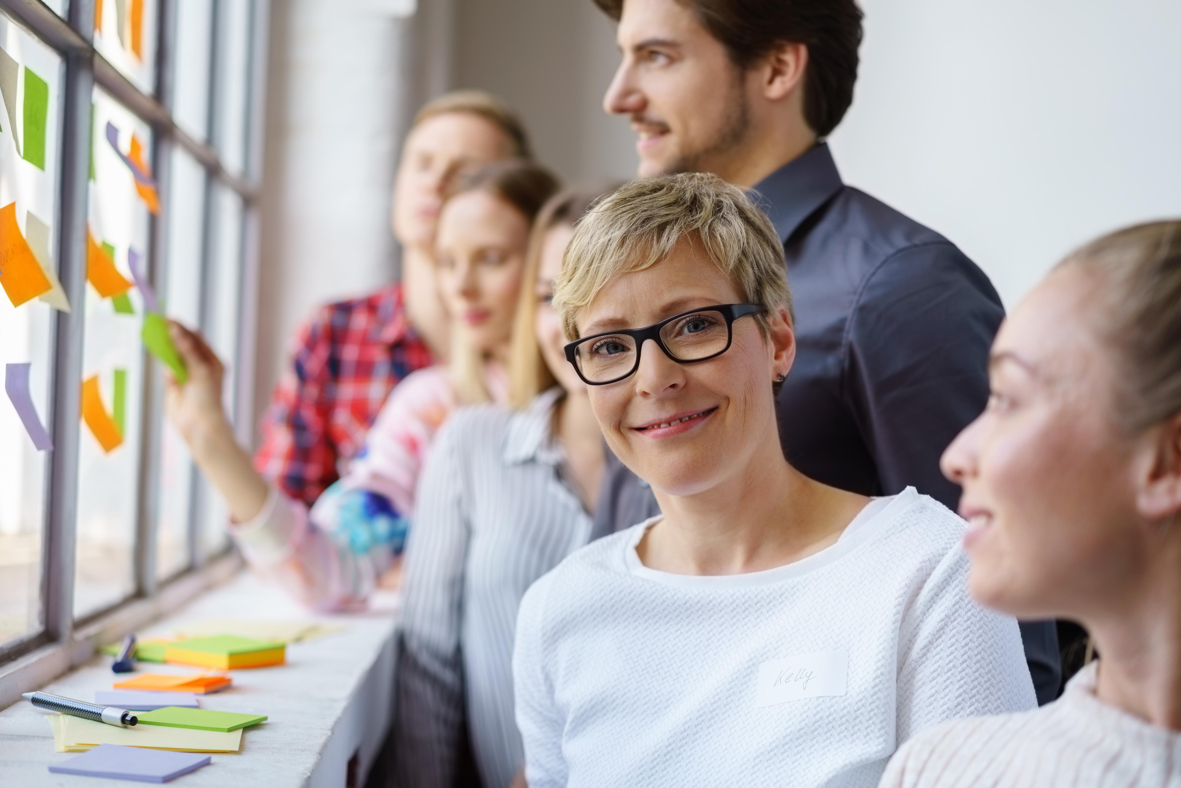 lächelnde frau arbeitet im team in einem workshop