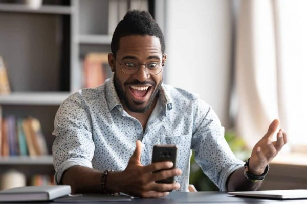 Overjoyed african business man using smartphone excited about mobile win
